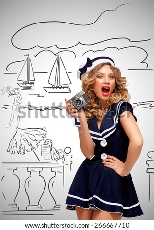 Retro photo of a glamorous pin-up sailor girl posing and taking a photo of a seashore and tourists with an old vintage photo camera on grey sketchy background. - stock photo