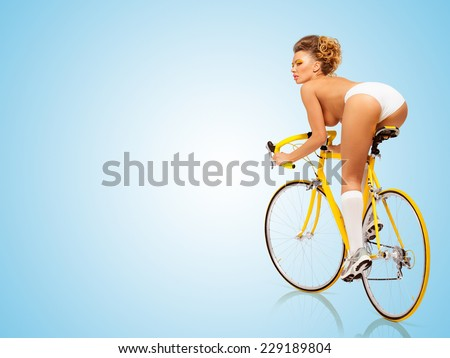 Retro photo of a nude sexy pin-up girl in white erotic panties riding a yellow racing bicycle on blue background. - stock photo