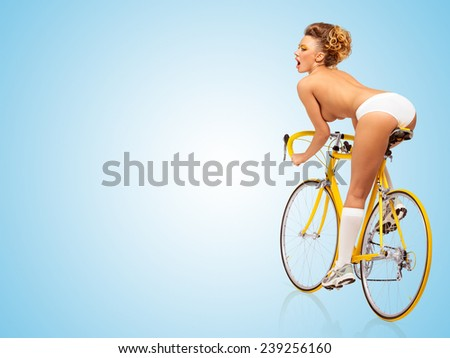 Retro photo of a nude sexy pin-up girl in white panties riding a yellow racing bicycle on blue background. - stock photo