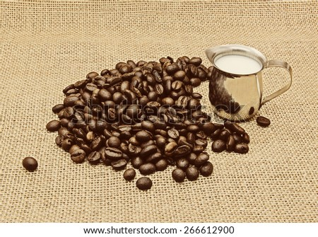 Retro photo of coffee beans on burlap background.