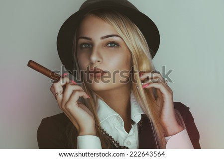 Retro photo of cute blonde woman with cigar in studio - stock photo