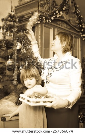 Retro photo of grandmother and child preparing for  Christmas at home - stock photo