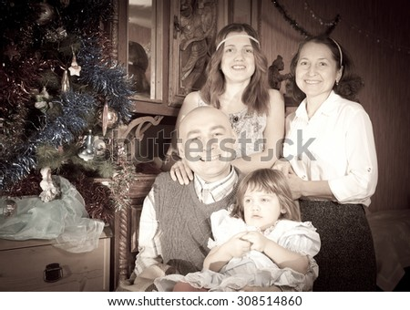 Retro photo of happy family of three generations at  home with  Christmas tree  - stock photo