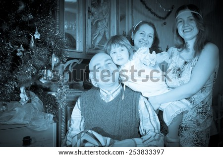 Retro photo of happy  family of three generations celebrating Christmas at home