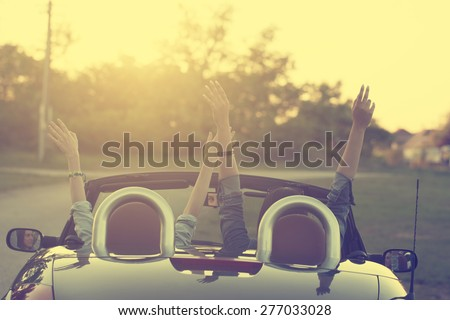 Retro photo of two happy traveler woman in cabriolet car - stock photo