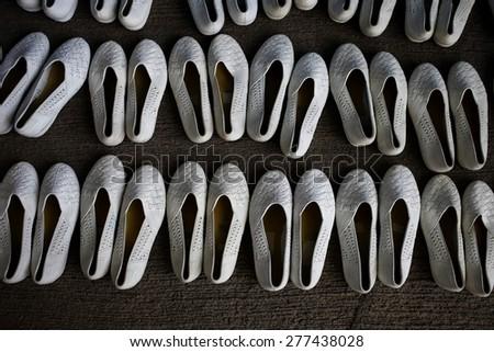 Retro photo of white color shoes on concrete background - stock photo