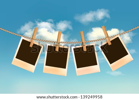 Retro photos hanging on a rope in front of a blue sky with clouds. Raster version of vector. - stock photo