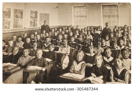 Retro picture of classmates. Group of children in the classroom. Vintage photo from 1920 with original film grain, blur and scratches. - stock photo