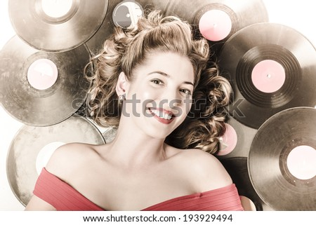 Retro pin-up woman with rocking hairstyle laying down some music against a set of 78rpm vintage vinyl records in classic fashion style - stock photo