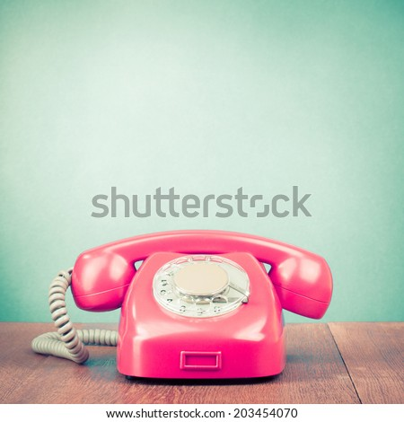 Retro pink rotary telephone on wooden table front mint green wall background - stock photo