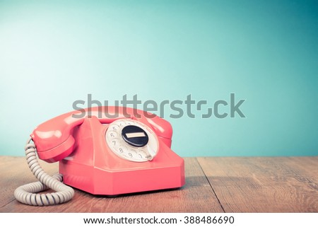Retro pink telephone on table front mint green background. Old style filtered photo