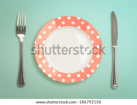 Retro polka dot plate with fork and knife top view - stock photo