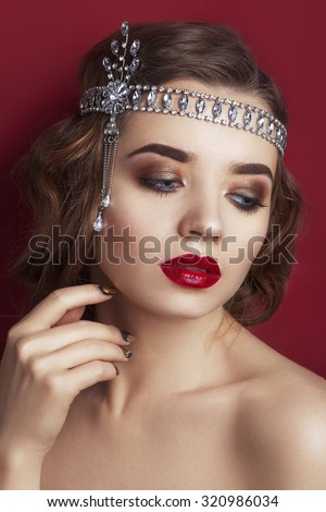 Retro portrait of a beautiful woman on a red Background.. Vintage style. Fashion Beauty photo. woman with curly hair and evening make-up. Jewelry and Beauty. Red lips. Picture taken in the studio - stock photo