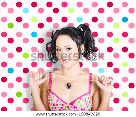 Retro portrait of a beauty glamour and fashion girl holding gold necklace jewellery with diamond pendant on colourful polka-dot background - stock photo