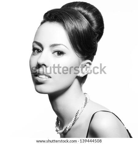 Retro portrait of a smiling beautiful woman with luxurious necklace and great hairdo. Jewelry and Beauty. Vintage (Hollywood) style. Classic old movie star. Close-up. Black and white studio shot - stock photo