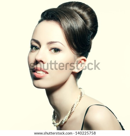 Retro portrait of a smiling beautiful woman with luxurious necklace and great hairdo. Jewelry and Beauty. Vintage (Hollywood) style. Classic old movie star. Healthy teeth. Close-up. Studio shot - stock photo