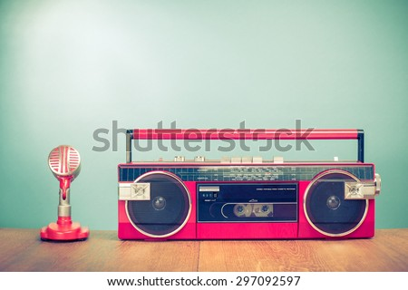 Retro radio cassette recorder from 80s and microphone front mint green background. Vintage old instagram style filtered photo