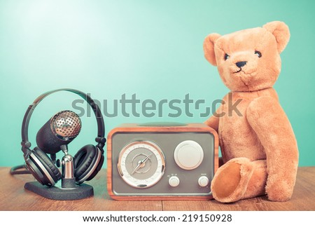 Retro radio, microphone with headphones and Teddy Bear front mint green background - stock photo