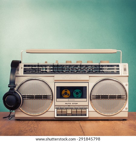 Retro radio recorder from 80s and headphones front mint green background. Vintage old style instagram filtered photo