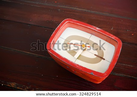 Retro red alarm clock on the wooden background. Toned image. Top view. - stock photo