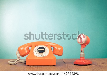 Retro red microphone and telephone on table front mint green background - stock photo