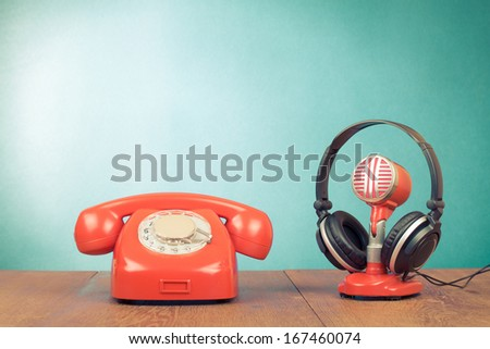 Retro red microphone, headphones and telephone on table front mint green background - stock photo