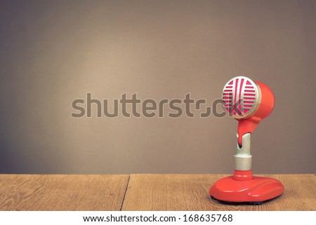 Retro red microphone on table for background - stock photo