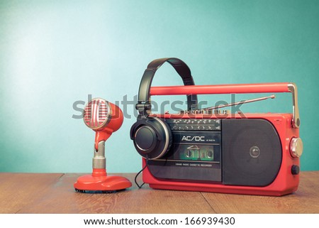 Retro red radio cassette player, microphone, headphones on table - stock photo