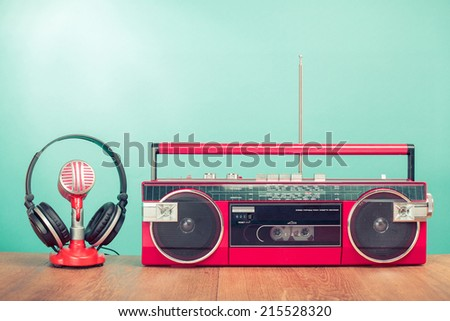 Retro red radio recorder, microphone and headphones front mint green background - stock photo