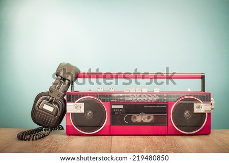 Retro red radio tape recorder and old headphones front gradient background - stock photo