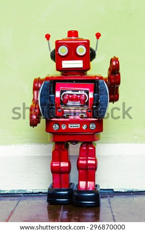 retro red robot toy on a wooden floor  - stock photo