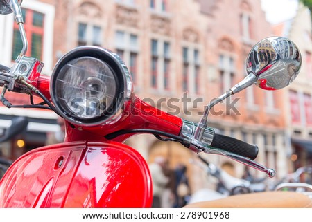 Retro red scooter in old town street. Horizontal oriented photo - stock photo