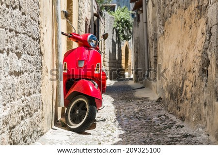 Retro red scooter old town narrow street. Horizontal oriented photo. - stock photo