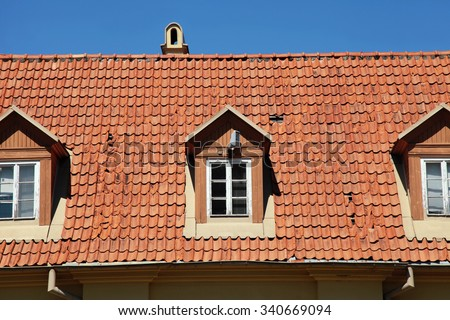 Retro red tile roof of old house - stock photo
