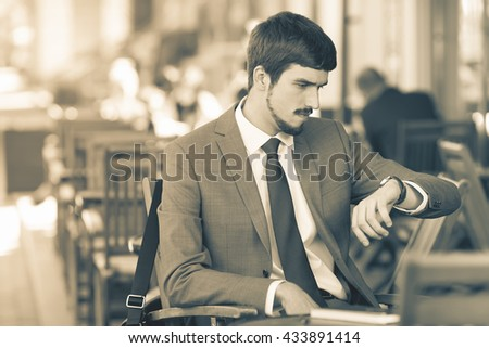 Retro revival image of handsome man looking time at watch. Waiting and sitting at sidewalk cafe outdoors. Executive businessman dressed in fashion costume. Stylish man. Punctuality