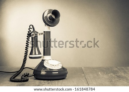 Retro rotary telephone on table with empty place for vintage background - stock photo