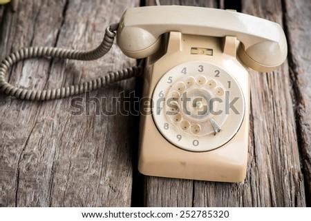 Retro rotary telephone on wood background. - stock photo