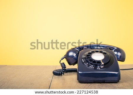 Retro rotary telephone on wood table front yellow wall - stock photo