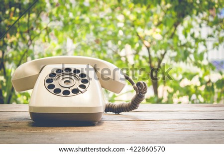 Retro rotary telephone on wood table vintage filter - stock photo