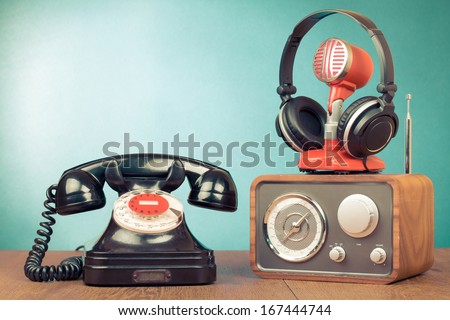 Retro rotary telephone, radio, headphones, microphone on table - stock photo