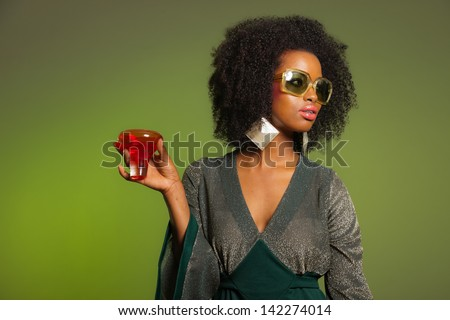 Retro 70s afro fashion woman with green dress and orange cocktail glass. Green background. - stock photo