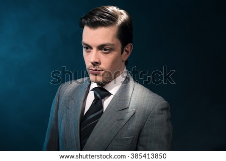Retro 1940s business man in suit and tie against blue wall. - stock photo