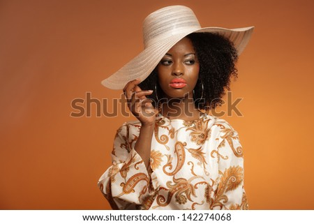 Retro 70s fashion afro woman with paisley dress and white hat. Brown background.