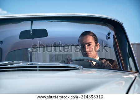 Retro 60s fashion business man wearing grey suit with tie sitting in classic car. - stock photo
