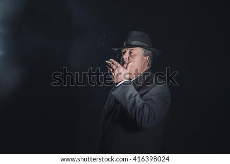 Retro 1940s gangster smoking cigar. Classic studio portrait. - stock photo