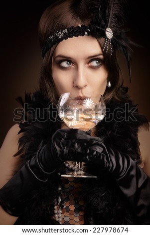 Retro 20s style woman drinking champagne - Portrait of a flapper girl at a party  - stock photo