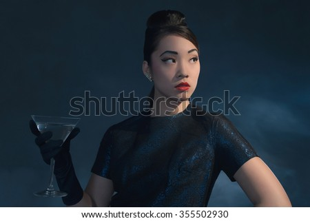 Retro 40s styled Asian woman in evening dress with cocktail glass. - stock photo