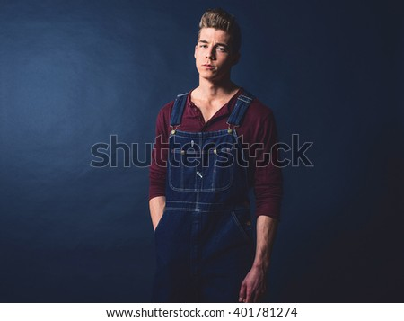 Retro 1950s worker fashion man wearing jeans bib and brace. - stock photo