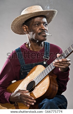 Retro senior afro american blues man in times of slavery. Wearing denim bib and brace overall with straw hat. Playing acoustic guitar.