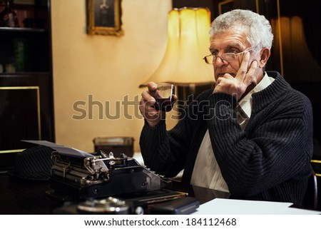 Retro Senior man writer with glasses sitting at the desk with glass of whiskey and thinking.